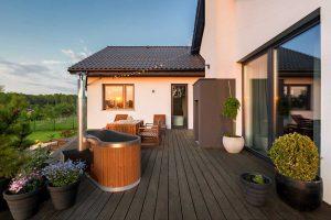 Schaffelbad mti Kunststoffeinsatz in Grau und Holzofen auf der Terrasse.